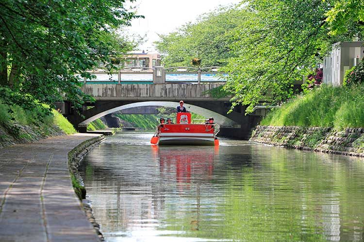 緑の中の松川遊覧船(安住橋を路面電車が通る)